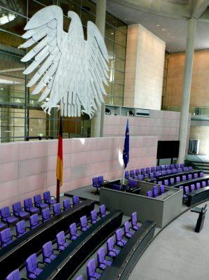Der Bundestag von innen. Man sieht den Bundesadler und die leeren Stuhlreihen des Kabinetts.