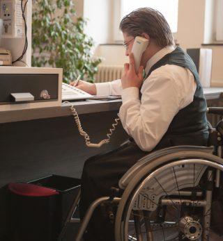 Ein Mann sitzt im Rollstuhl an einer Hotelrezeption.