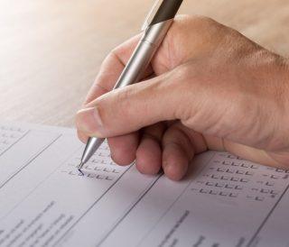 Hand mit Kugelschreiber füllt Fragebogen aus